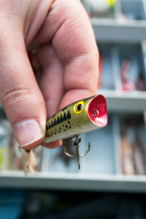 selects: A fishermen selects the lure from his tackle box that he is going to use. Shallow depth of field.