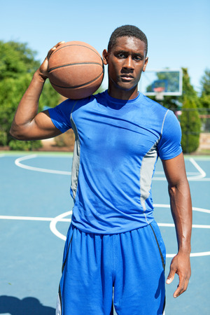early twenties: Young basketball player in his early twenties posing on an outdoor court.