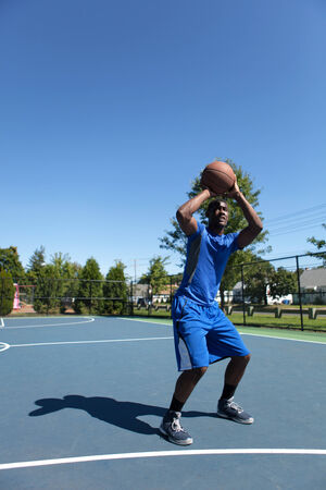 baller: Young basketball player in his early twenties shooting the ball on an outdoor court. Stock Photo