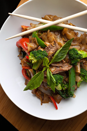 Pad kee mao drunken noodle thai dish with beef and mixed vegetables. photo