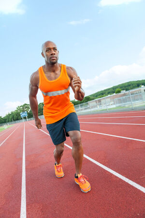 momentum: African American man in his 30s running at a sports track outdoors.