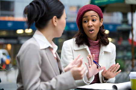 Two business women having a casual meeting or discussion in the city. photo