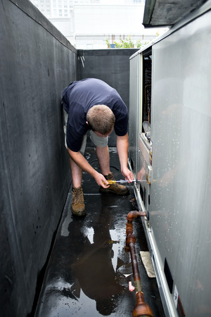 An HVAC heating ventilating air conditioning technician repairing or maintaining a large commercial unit. photo