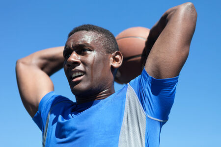 early twenties: Young basketball player in his early twenties posing with the ball held behind his head. Stock Photo