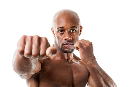 Ripped and muscular martial artist holding his fists up isolated over a white background. Great boxing or fitness concept. Shallow depth of field. photo