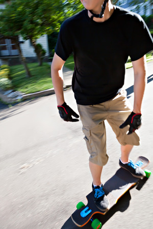 action shot: Action shot of a longboarder skating on an urban road. Slight motion blur. Stock Photo