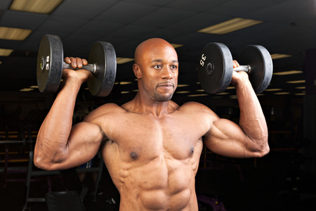 jacked: Toned and ripped lean muscle fitness man lifting weights.
