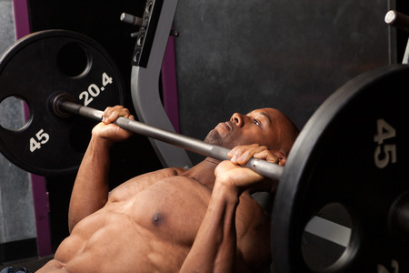 body builder: Weight lifter at the bench press lifting a barbell on an incline bench.