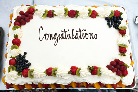 White frosted cake with a fruit border and the message that reads Congratulations.