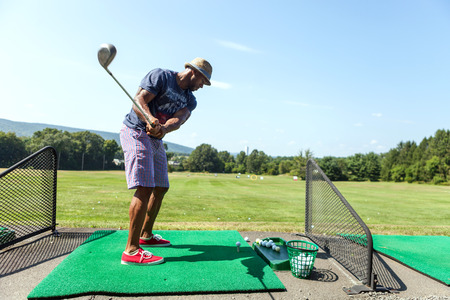 Men exercise: Athletic golfer swinging at the driving range dressed in casual attire. Kho ảnh