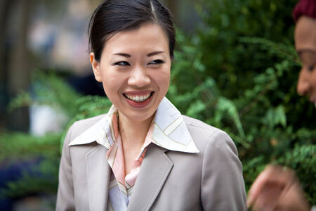 An attractive Asian woman dressed in business attire laughing at the words of her business associate. photo