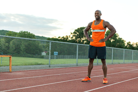 track and field athlete: African American man in his 30s posing at a sports track outdoors.