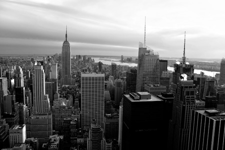 Horizontal aerial view of the Manhattan section of New York City including all of the buildings and skyline in black and white.