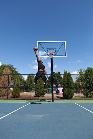 baller: Young basketball player flying to the hoop for a monster jam. Stock Photo