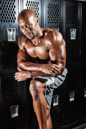 Portrait of a lean toned and fit muscular man under dramatic low key lighting. photo