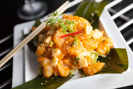 Thai crispy shrimp dish with apple and sesame seeds presented beautifully on a white square plate with chopsticks. photo