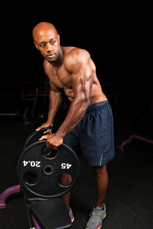 jacked: Toned and ripped lean muscle fitness man lifting plate weights.