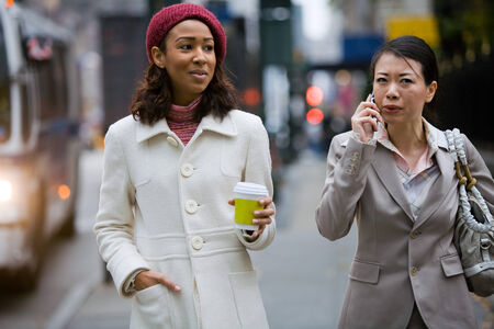 sidewalk talk: Two business women walking in the big city. One is on her cell phone.