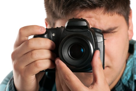 Male Photographer Shooting digital slr camera isolated on white.  Shallow depth of field. photo