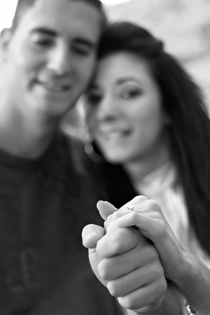 Young happy couple holding a diamond engagement ring.  Shallow depth of field with sharp focus on the ring. photo