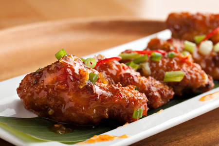 Thai style spicy chicken wings appetizer on a contemporary white plate.