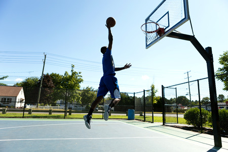 dunk: Young basketball player driving to the hoop for a high flying slam dunk.