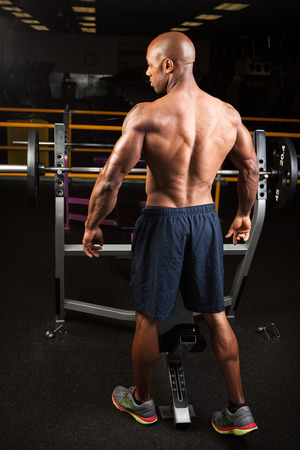 lats: Toned and ripped lean muscle fitness man standing by a weight bench at the gym. Stock Photo