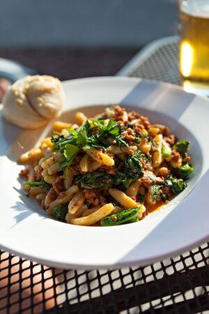 comida: Broccoli rabe prato com salsicha sobre o macarrão penne apresentado em um prato branco. Imagens