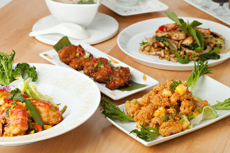 close up food: Varieties of Thai foods and appetizers covering a table. Shallow depth of field. Stock Photo