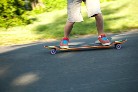 action shot: Action shot of a longboarder skating on a suburban road. Shallow depth of field.