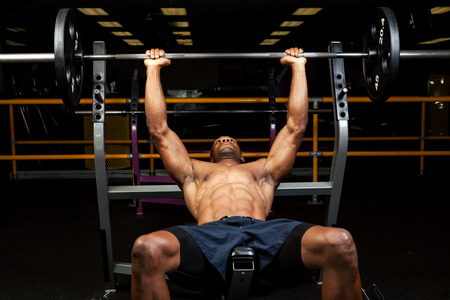 Weight lifter at the bench press lifting a barbell on an incline bench.