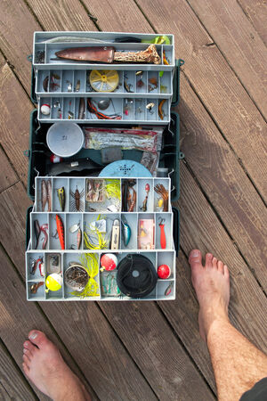 stocked: A large fishermans tackle box fully stocked with lures and gear for fishing.