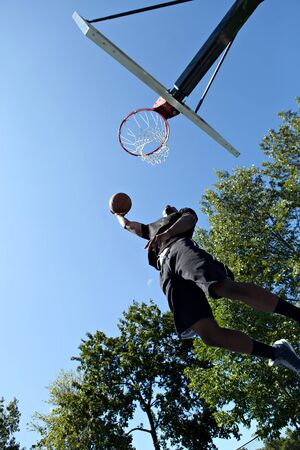 basketball dunk: Young basketball player driving to the hoop for a high flying slam dunk.