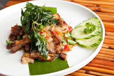 santa cena: Tradicional plato de cerdo crujiente tailandés con guarnición verde.