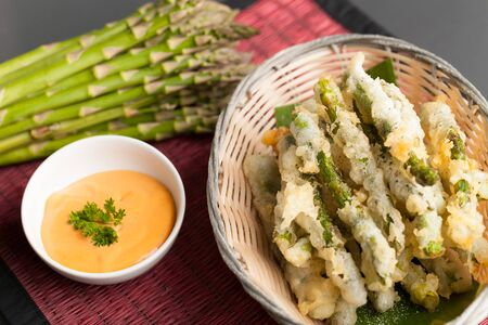 Thai style appetizer of fried tempura asparagus with dipping sauce. Reklamní fotografie
