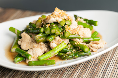 Freshly prepared Asian style chicken and asparagus stir fry with garlic. Stock Photo