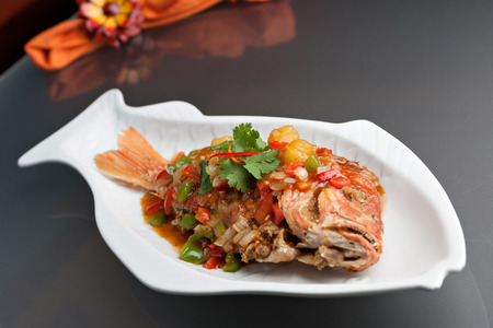 sweet course: Freshly prepared Thai style whole fish red snapper dinner with tamarind sauce on a white fish shaped plate. Shallow depth of field.
