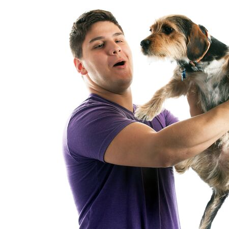 High key portrait of a young man holding a cute mixed breed dog isolated over white. photo