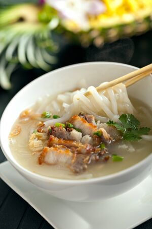 Closeup of a person eating Thai style crispy pork rice noodle soup from a bowl with chopsticks. Pineapple fried rice in the background. photo
