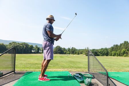 driving range: Athletic golfer teeing up at the driving range dressed in casual attire.