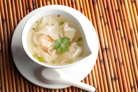 ton: Thai shrimp wonton soup bowl close up with spoon.