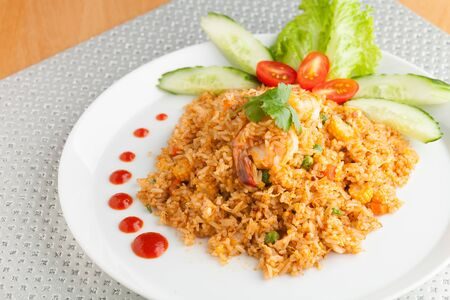plating: Sriracha shrimp fried rice dish with garnish dots of siracha sauce. Stock Photo