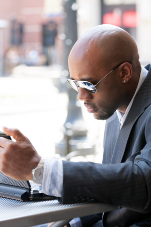early 30s: A business man in his early 30s working on his laptop or netbook computer outdoors. Stock Photo