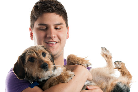 High key portrait of a young man holding a cute mixed breed dog isolated over white. Shallow depth of field with focus on the mans face. photo