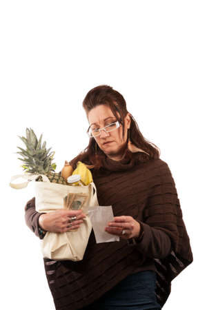 frugal: Middle aged woman carefully examining her register receipt reviewing her grocery shopping bill.