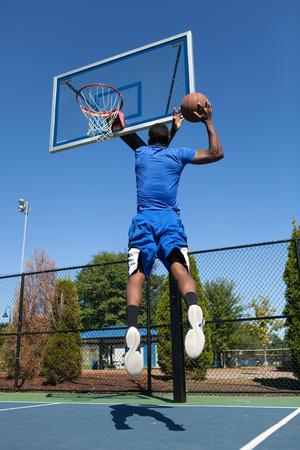 canestro basket: Giovane giocatore di basket di guida al cerchio per una slam dunk alta quota. Archivio Fotografico