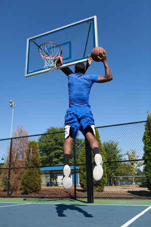 hoop: Young basketball player driving to the hoop for a high flying slam dunk.