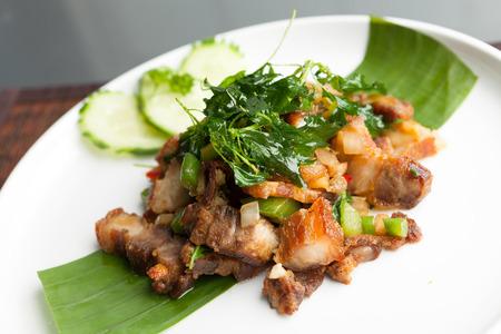 Traditional Thai crispy pork dish with green garnish. photo