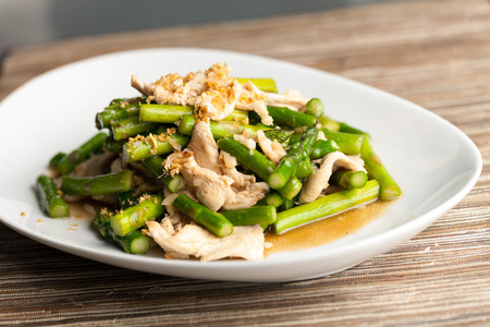 Freshly prepared Asian style chicken and asparagus stir fry with garlic. 免版税图像