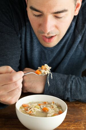 Man eating a hot bowl of fresh homemade chicken soup.